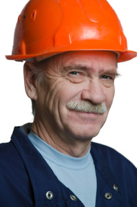 A happy man wearing an orange protective headgear.